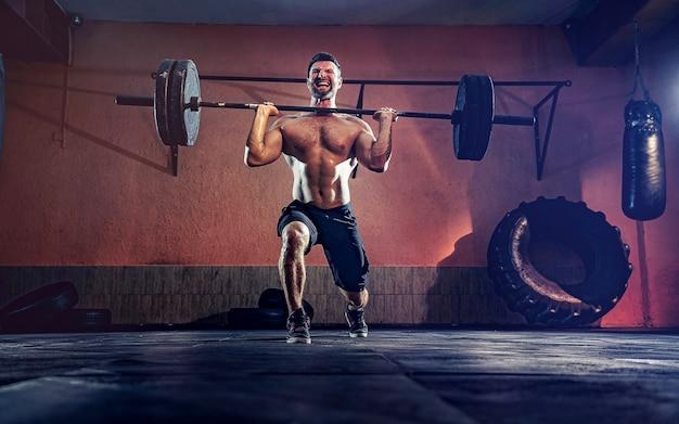 彼のガレージ、自己隔離でバーベル突進をしている筋肉のフィットネス男。ファンクショナルトレーニング。スナッチエクササイズ。