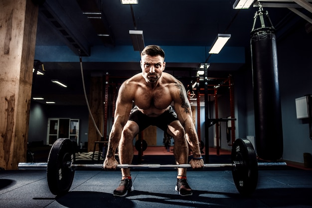 Мускулистый фитнес человек делает тягу со штангой в современном фитнес-центре