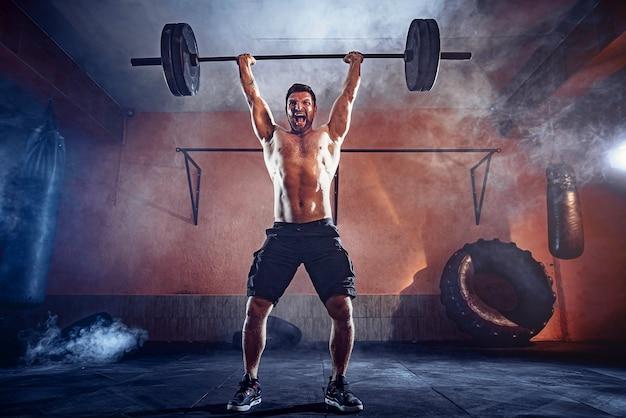 현대적인 피트니스 센터에서 그의 머리 위로 바벨 데 드리프트를하고 근육 피트니스 남자. 기능 훈련. 날치기 운동. 벽에 연기.