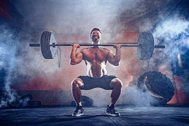 現代のフィットネスセンターで彼の頭の上にバーベルをデッドリフトしている筋肉のフィットネス男。ファンクショナルトレーニング。スナッチエクササイズ。壁に煙が出る。