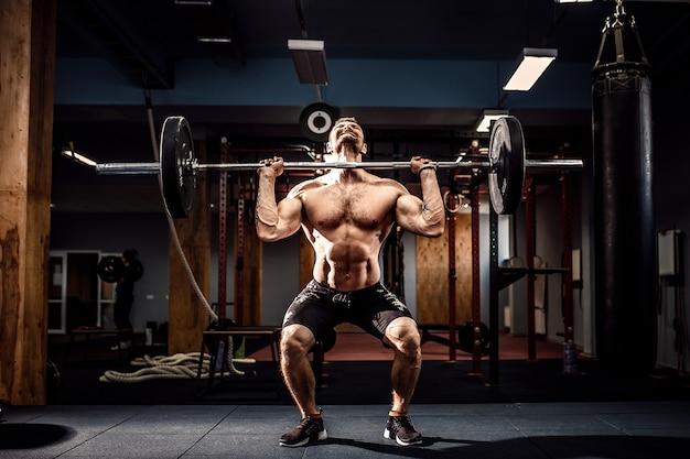 Мускулистые фитнес человек делает становую тягу штангу над головой в современном фитнес-центре. функциональная тренировка.