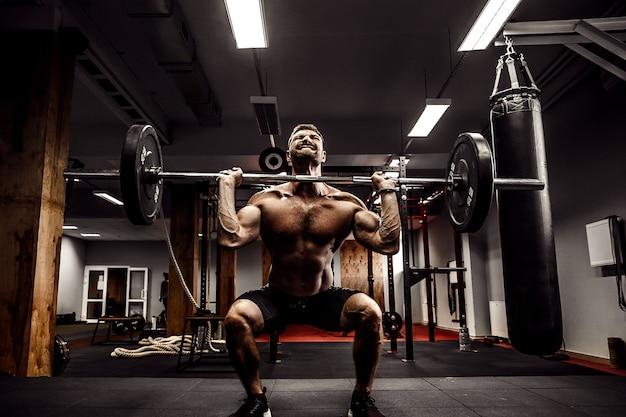 Мускулистый фитнес человек делает тягу со штангой над головой в современном фитнес-центре