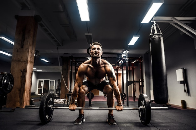 Muscular fitness man doing deadlift a barbell over his head in modern fitness center