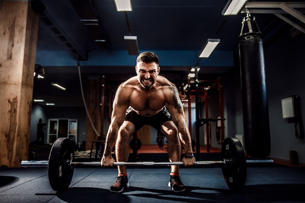Muscular fitness man doing deadlift a barbell in modern fitness center