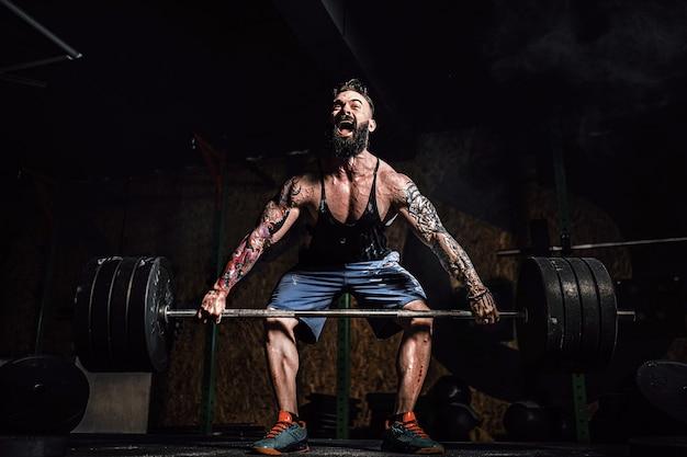 現代のフィットネスセンターでバーベルのデッドリフトをしている筋肉のフィットネス男。ファンクショナルトレーニング。スナッチエクササイズ