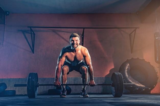筋肉質のフィットネスマンが、ガレージでバーベルを頭上に押し込み、自己隔離します。ファンクショナルトレーニング。スナッチエクササイズ。