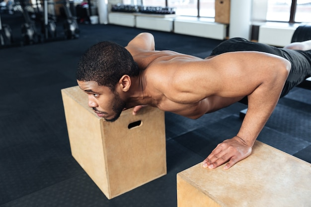 Muscular fitness man doing push-ups in the gym using sports equipment