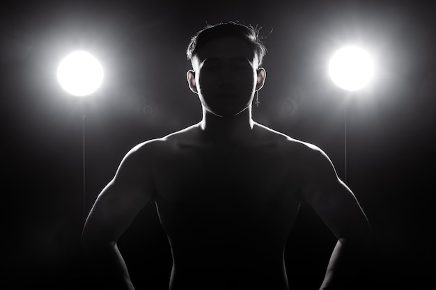 Muscular fitness man exercises healthy lifestyle in dark background silhouette back light