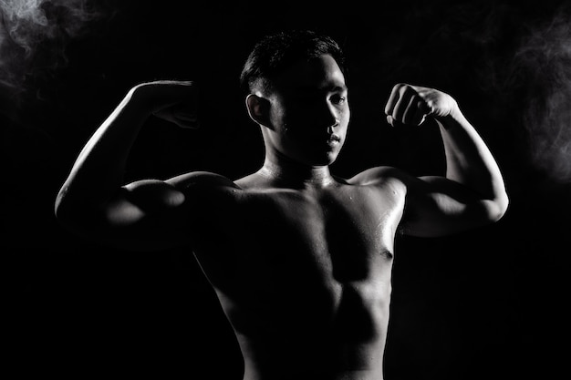 Muscular fitness man exercises healthy lifestyle in dark background silhouette