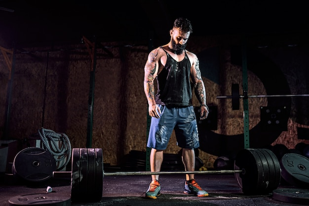 現代のフィットネスセンターでバーベルをデッドリフトする準備をしている筋肉のフィットネス男。ファンクショナルトレーニング。スナッチエクササイズ