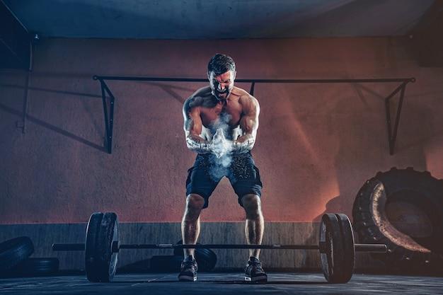 現代のフィットネスセンターで彼の頭の上にバーベルをデッドリフトする準備をしている筋肉のフィットネス男。ファンクショナルトレーニング。スナッチエクササイズ。