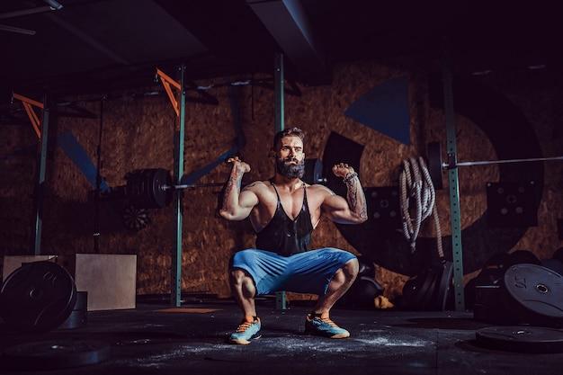 現代のフィットネスセンターで彼の頭の上にバーベルをデッドリフトする準備をしている筋肉のフィットネス男。ファンクショナルトレーニング。スナッチエクササイズ