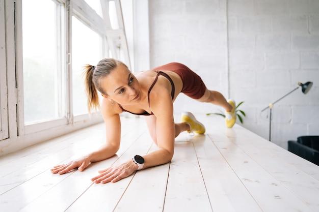窓枠で脚のトレーニングをしているスポーツウェアを身に着けている完璧なアスリートボディを持つ筋肉フィットネスの若い女性は、目をそらします。健康的なライフスタイルと家庭での身体活動の概念。