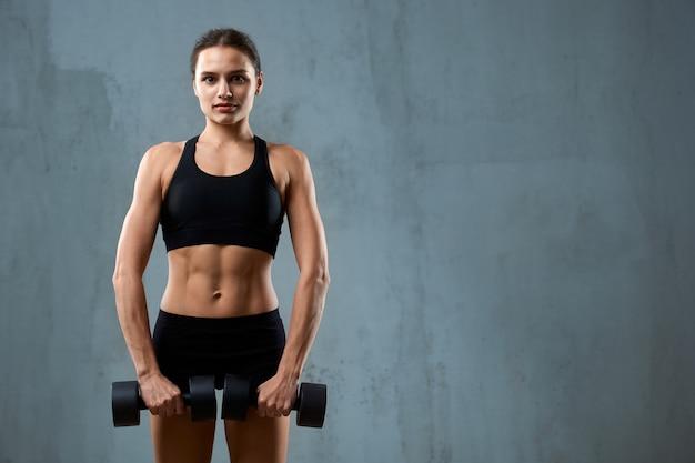 Мускулистая фитнес-женщина с гантелями