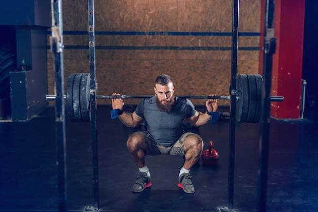 Мышечная сосредоточены битник в спортивной одежде, поднимая штанги в положении на корточках.