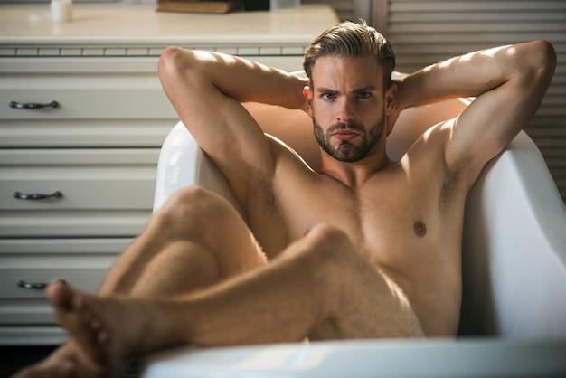 豪華なバスタブでリラックスした筋肉のゲイの男。
