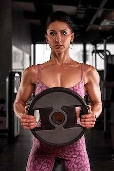 체육관에서 운동을하는 분홍색 스포츠 착용에 근육질 소녀