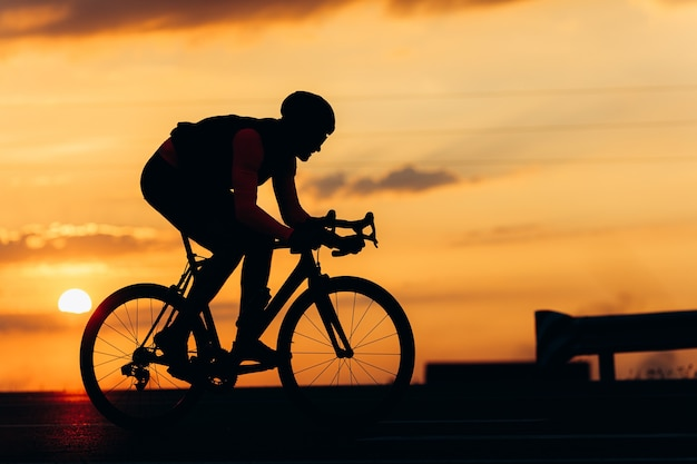 Muscular guy dressed in cycling clothing biking on fresh air during beautiful sunset