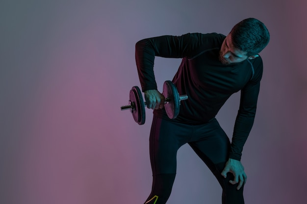 회색 스튜디오 벽에 무거운 무게로 어깨 근육을 펌핑, 아령으로 운동하는 운동복에 근육질의 남자. 스포츠, 보디 빌딩 및 활동적인 라이프 스타일 컨셉