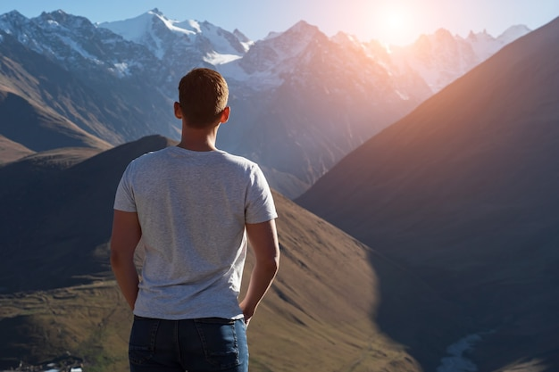 티셔츠를 입은 근육질의 남자가 밝은 가을 햇빛 뒷면의 하얀 눈 덮인 봉우리가 있는 갈색 록키 산맥을 바라보고 있다