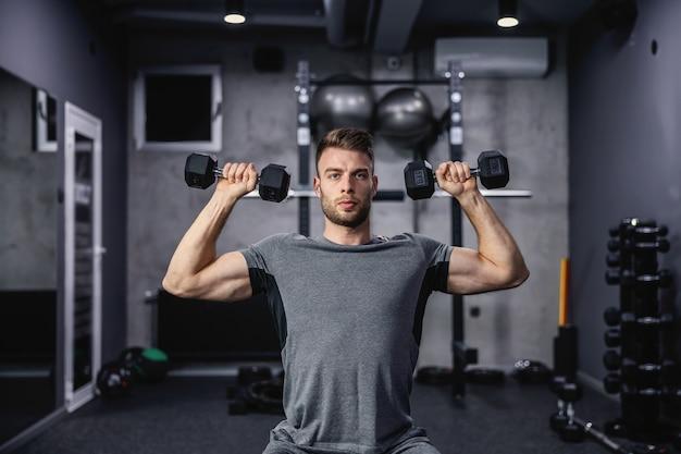 ジムのベンチに座ってダンベルを持ち上げる筋肉の男。トレーニング中にダンベルを使用している若いアスリート。体重で上腕二頭筋をポンピングする身体運動中の強い男
