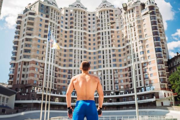 屋外でポーズをとる筋肉質の男。ハンサムな男の青いショートパンツの肖像画。