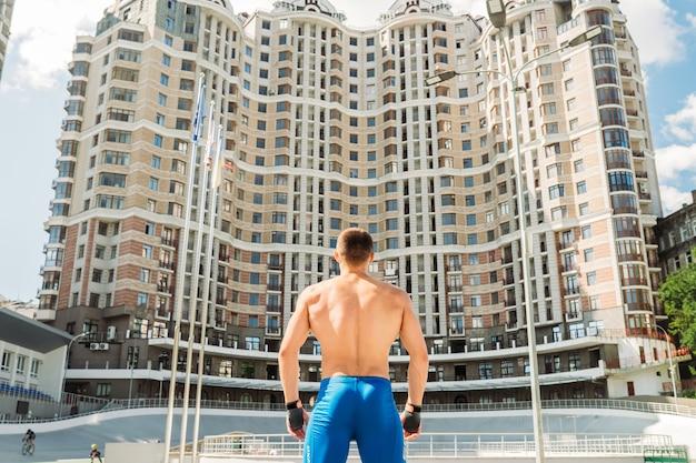 屋外でポーズをとる筋肉の男。ハンサムな男の青いショートパンツの肖像画。