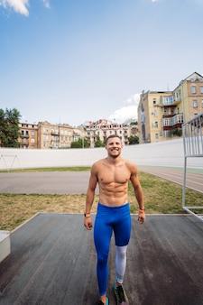 屋外でポーズをとる筋肉質の男。