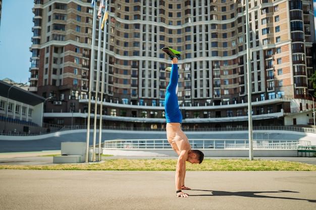 Ragazzo muscoloso sta sulle sue mani contro un edificio alto