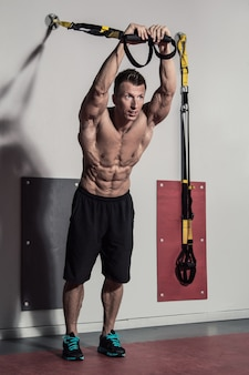 Muscular guy and suspension straps