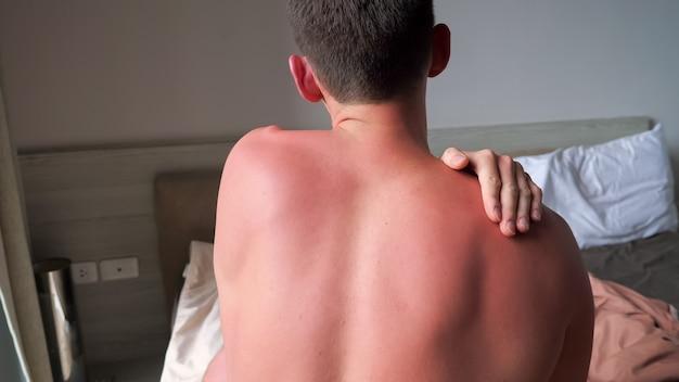 Мускулистый парень с голой спиной массирует шею и плечи руками, стоя у кровати в гостиничном номере, вид сзади