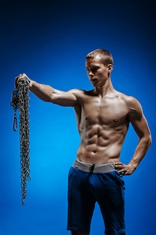 Muscular guy with chains on his shoulders against blue