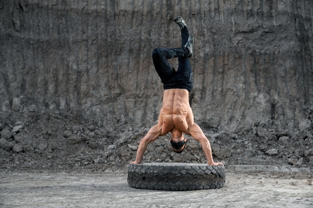 大きなタイヤに手を置いて立っている間、裸の胸のバランスをとっている筋肉質の男。黒のマスクとスポーツパンツを身に着けているアクティブな男性。持久力と強さの概念。