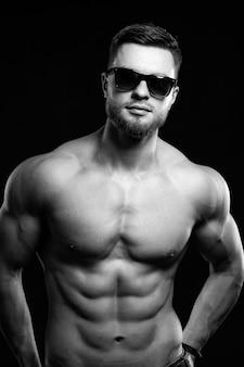 腰に手を当ててポーズをとる裸の胴体を持つ筋肉の男。スタジオ写真。ジーンズのハンサムな男の肖像画。黒と白。
