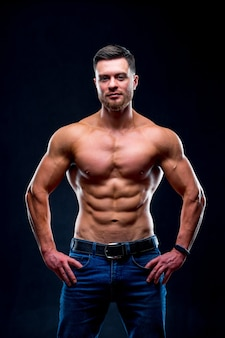 Мускулистый парень с голым торсом позирует с руками на талии