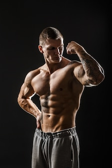 Muscular guy with tattoo. isolated on dark background