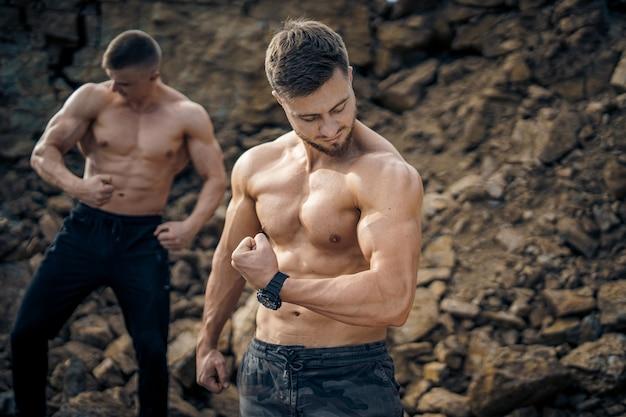 緊張した手でポーズをとる裸の胴体を持つ筋肉の男。屋外の写真。暗いズボンのハンサムな男性の肖像画。