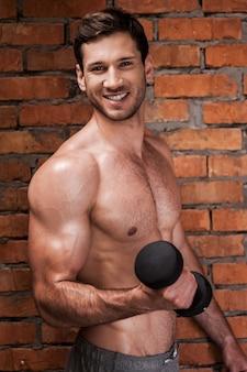 근육질의 건장함. 아령으로 훈련하는 쾌활한 젊은 근육질의 남자
