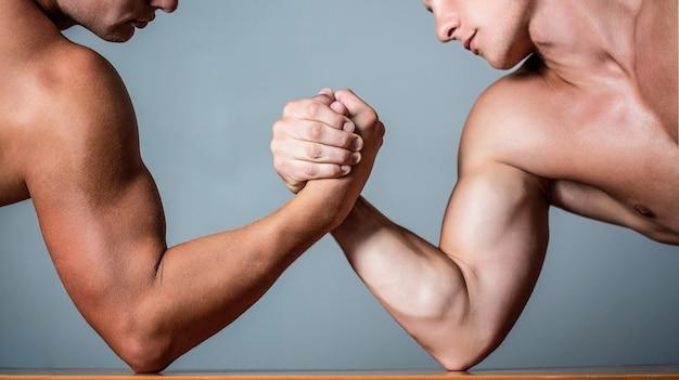 Мускулистая рука. сложный армрестлинг. двое мужчин по армрестлингу