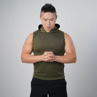 Мускулистый красивый азиатский мужчина без рукавов стоит серьезной изолированной серой стене