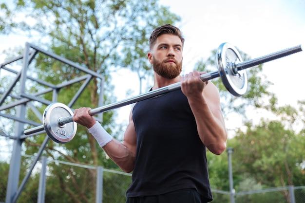 Мускулистый красивый бородатый мужчина тренировки со штангой на открытом воздухе