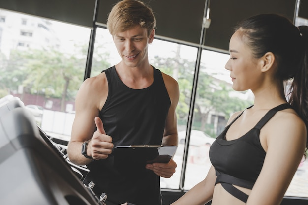 Muscular handsome caucasian personal trainer man showing thumbs up with young asian woman in fitness gym