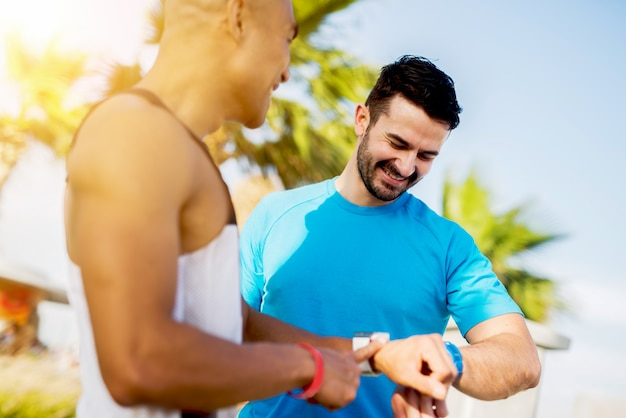 Muscular handsome men checking fitness trackers after hard work out