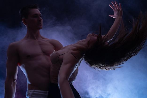 Мускулистый красивый сексуальный парень с красивой женщиной на темном фоне концепции романтической любви