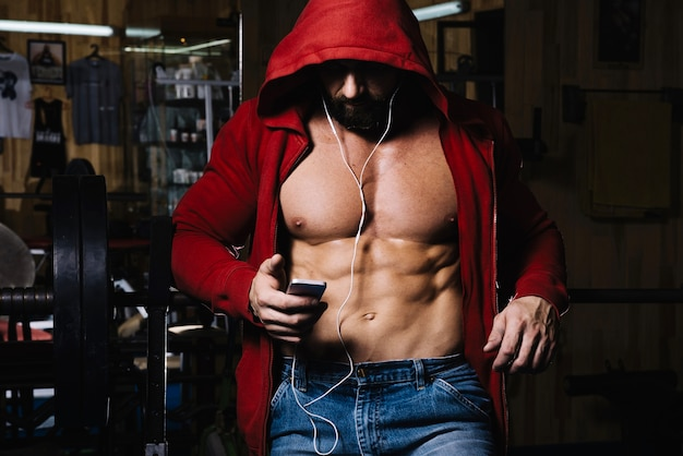 Muscular in hood with headphones