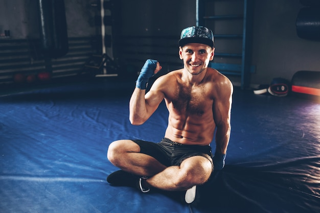 Muscular kick-box or muay thai fighter. a boxer shows his biceps. athlete sits in the gym