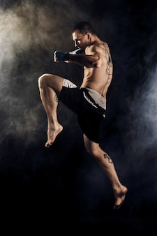 Muscular kickbox or muay thai fighter punching in jump. smoke