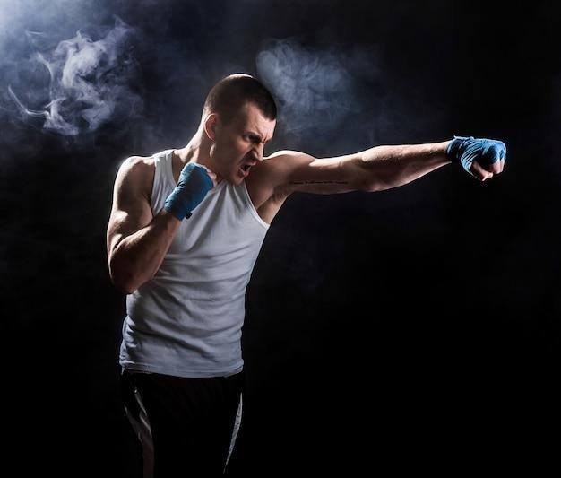 Muscular kickbox or muay thai fighter punching in smoke