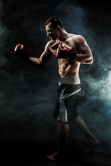 Muscular kickbox or muay thai fighter punching in smoke