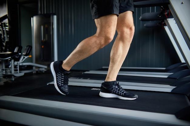 Muscular legs running on treadmill